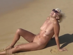 Naked blonde on a public nudist beach playing with a vibrator